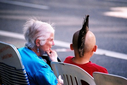 generation gap; old lady talking to boy with mohawk;