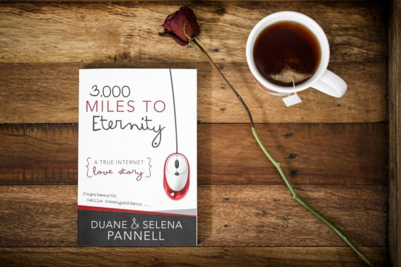 3,000 Miles To Eternity Book lying on wooden table with long stemmed rose and cup of tea